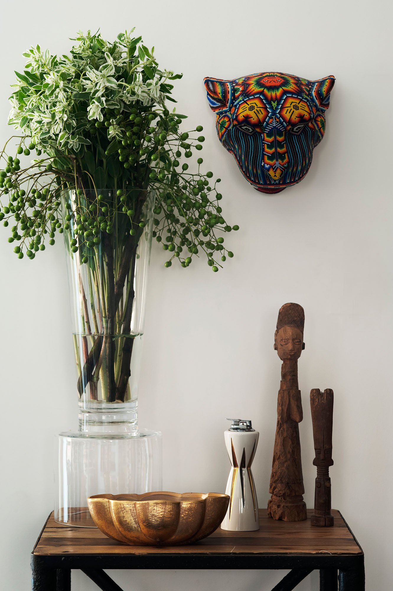 Flowers in Vase Near Artistic Wooden Ornament and Colorful Kitten Mask