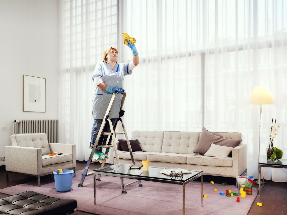 Lady Cleaning In Living Room