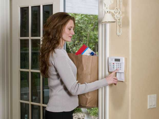 Honeywell woman at home keypad