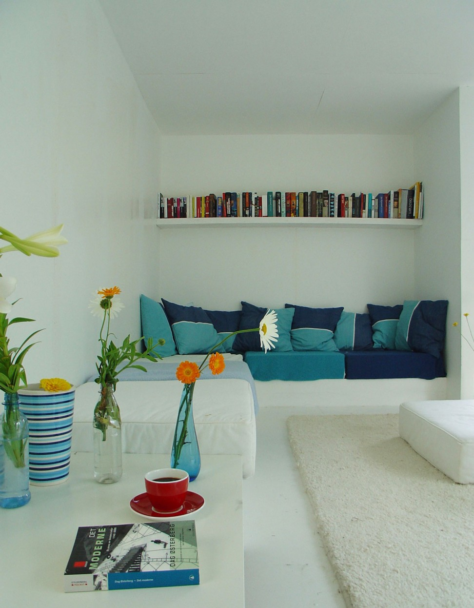 Colorful Flowers In Vase Placed On White Table With Blue Sofa View In Corner