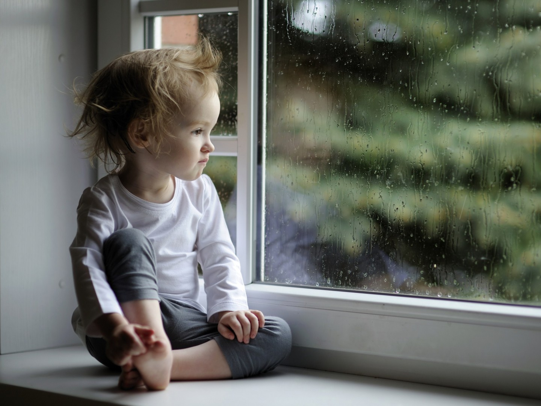 Baby Girl Enjoying Raindrop near Window Glass