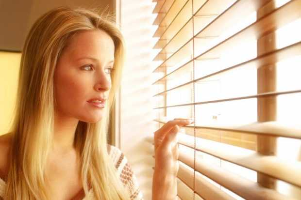 A Woman Looking outside through Timber Blinds Curtain
