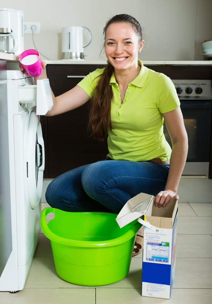 Cheerful Smiling Woman With Washing Detergent Doing Laundry At Home